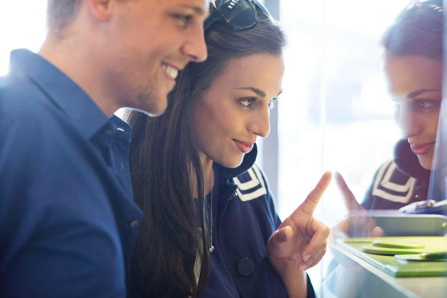 Young couple window shopping and pointing at glass