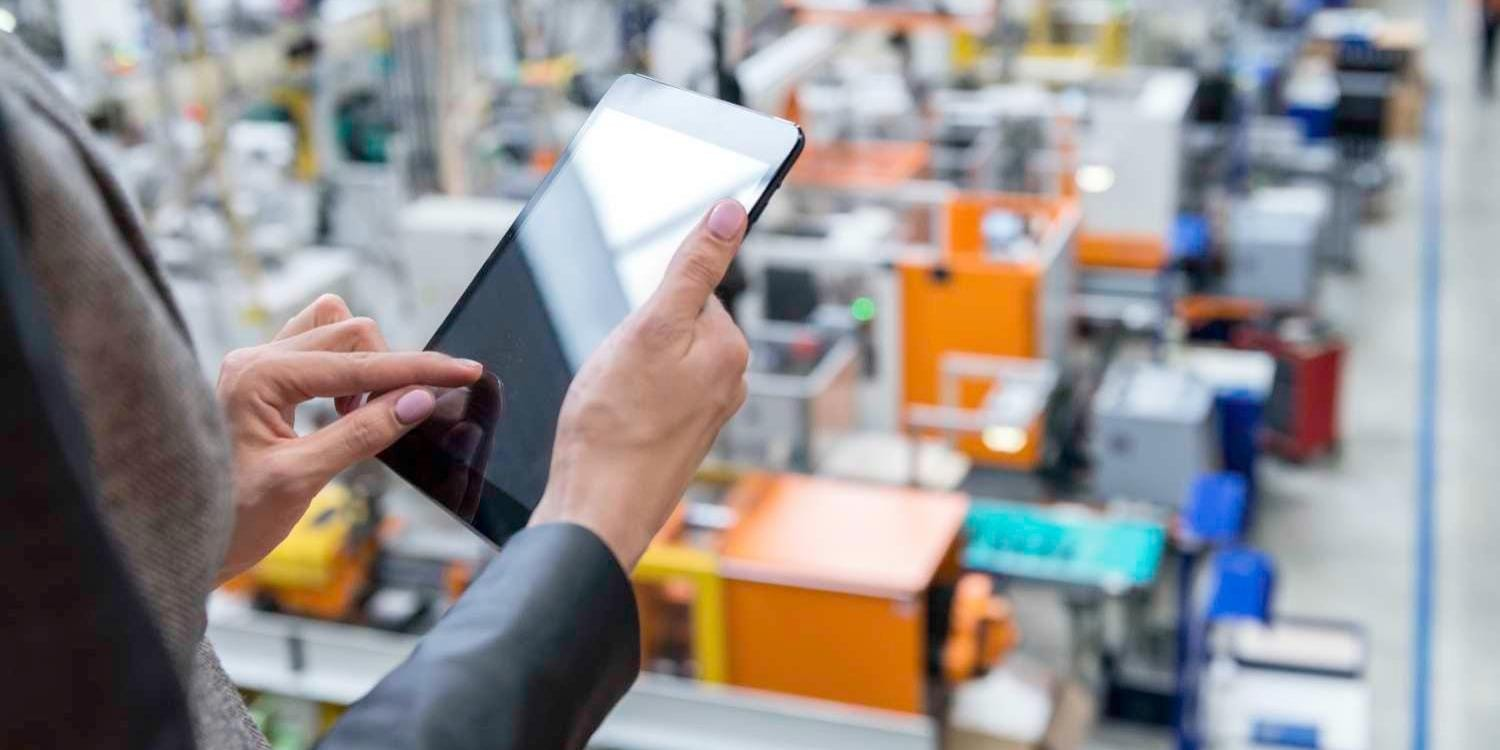 Operations executive using tablet device while overseeing shop floor