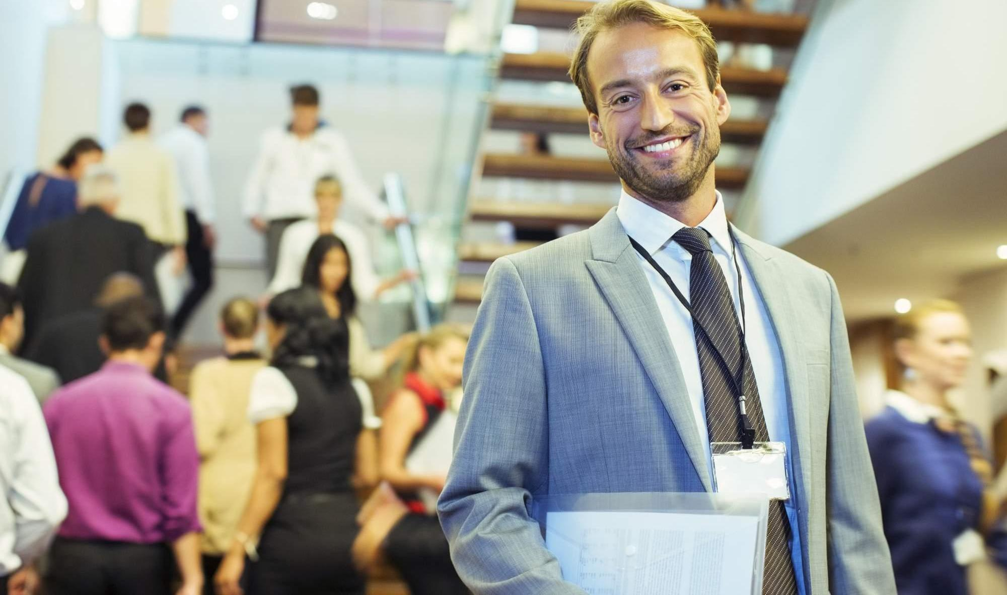 Portrait of smiling businessman standing in crowded lobby of conference center