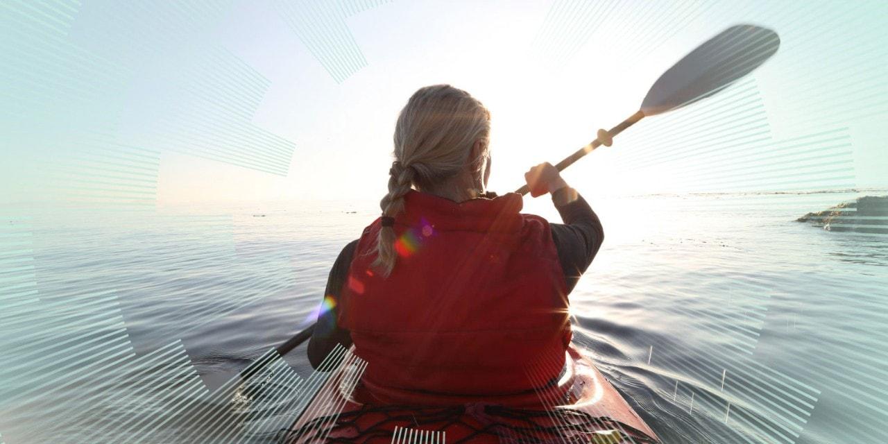 Woman paddles kayak on calm sea, towards sunrise