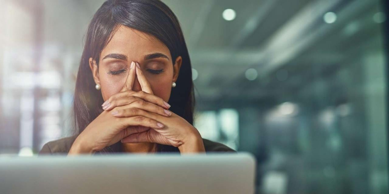 Young stressed and drained businesswoman in office