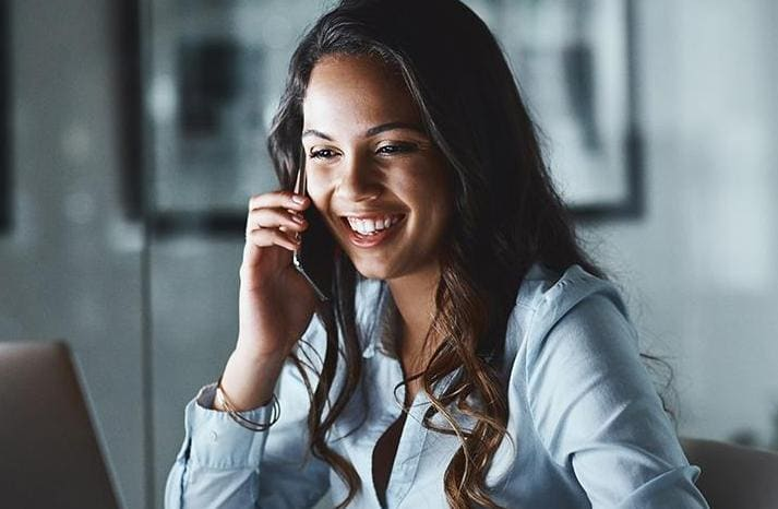 Young businesswoman using a mobile phone and laptop