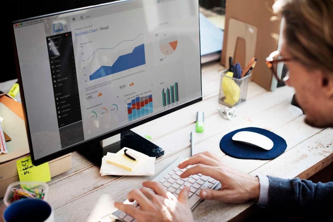 Man looking at charts on computer screen at wooden desk