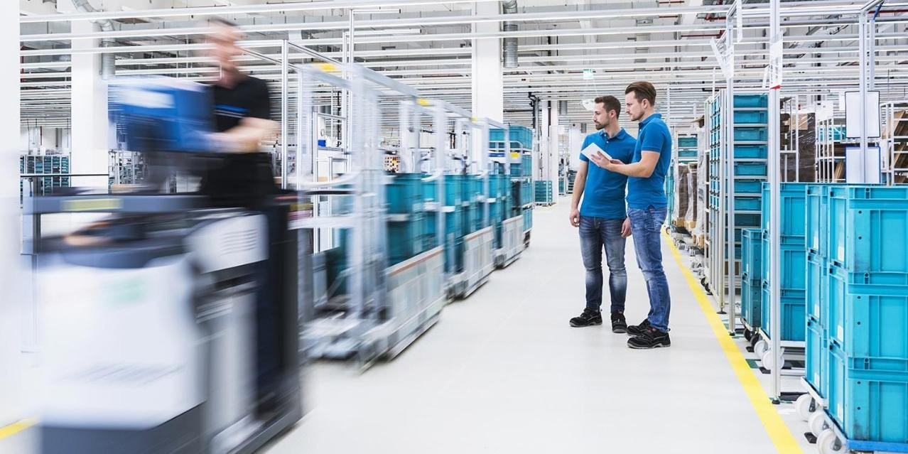 Two men with tablet talking in industrial hall while man driving a tugger train