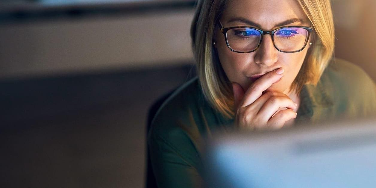 Young businesswoman working late on a computer in an office