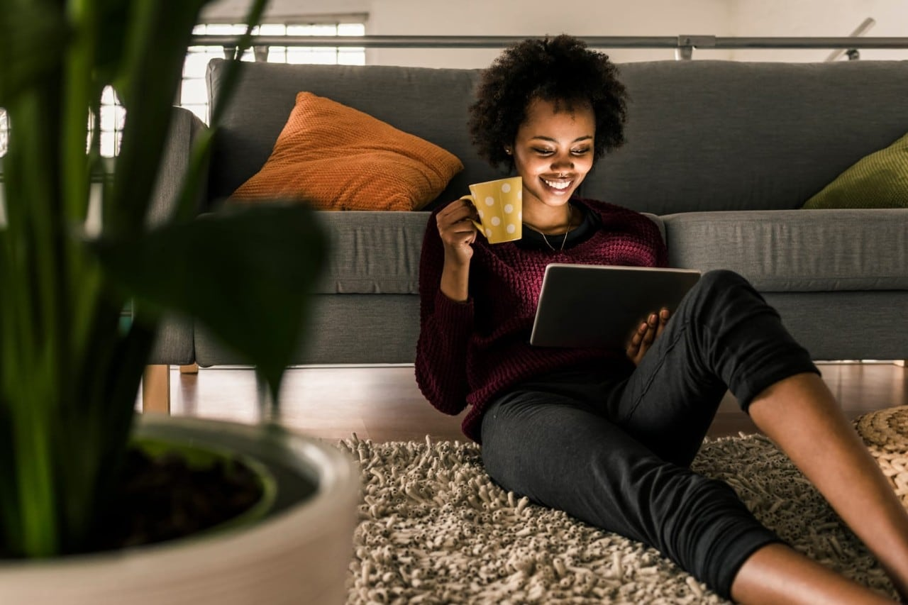 Smiling young woman at home holding cup and tablet