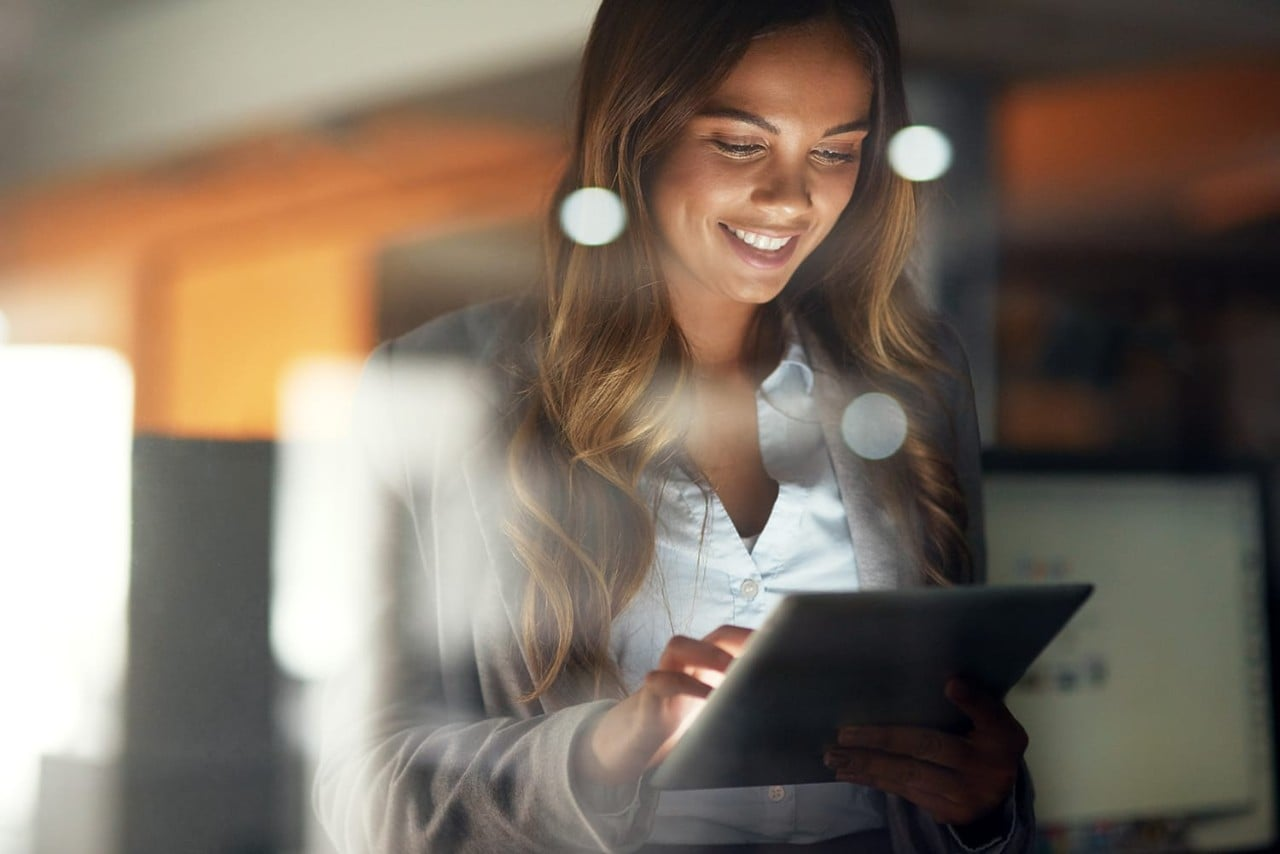 Young businesswoman with tablet working late in modern office