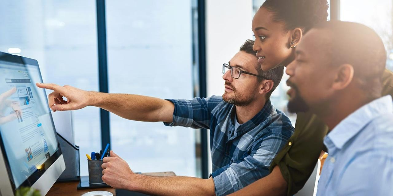 Three business people working around the computer in office