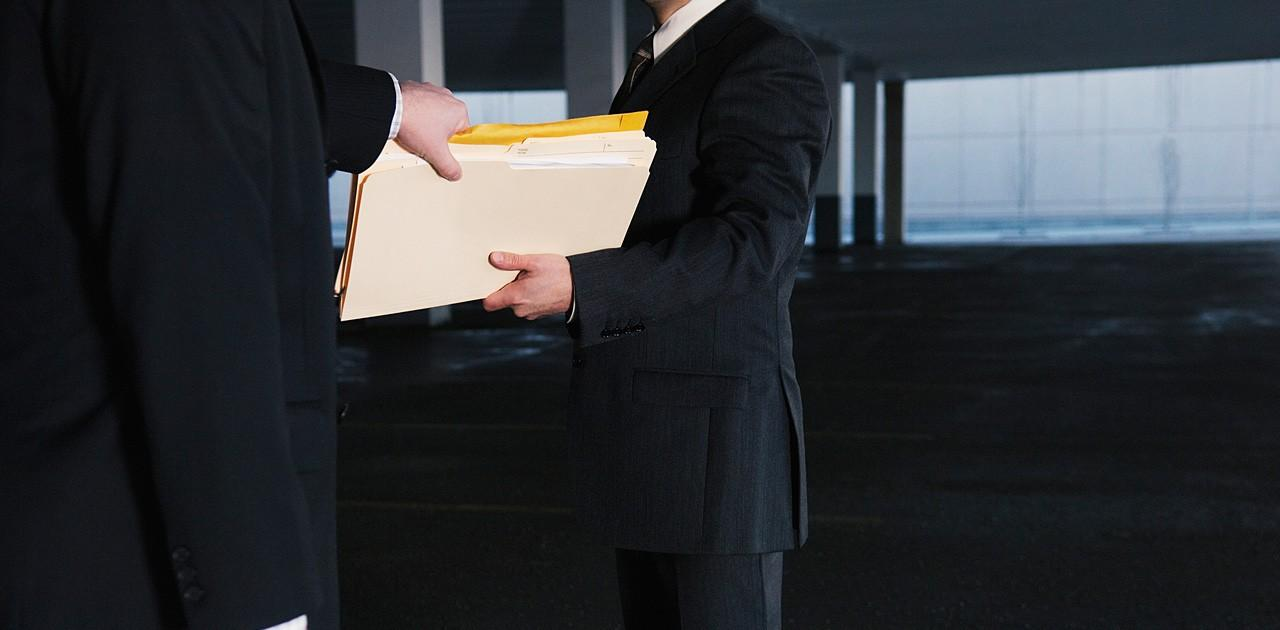 Two businessmen exchanging files –  possibly for procurement fraud