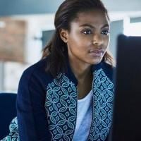 Black Woman working behind a computer in the office