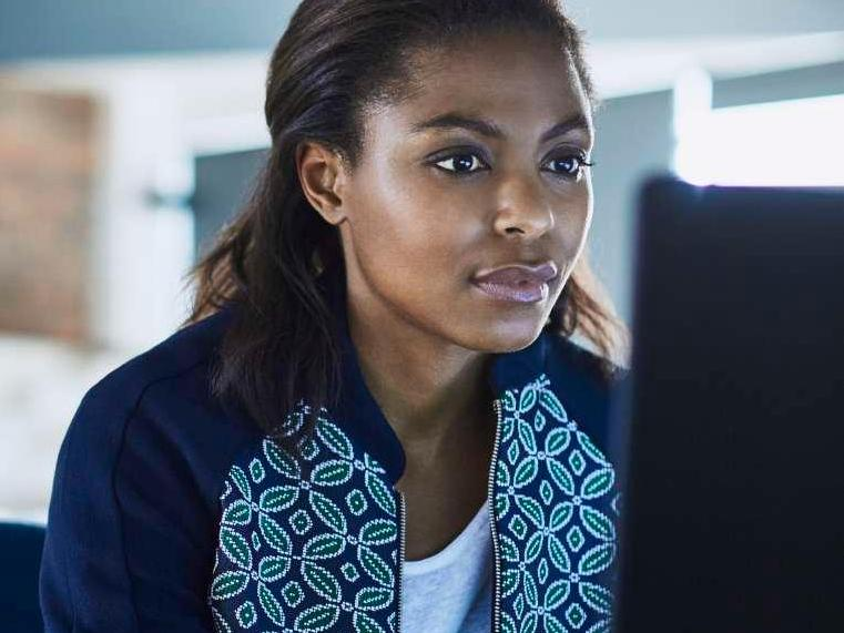 Black Woman in patterned sweater at computer