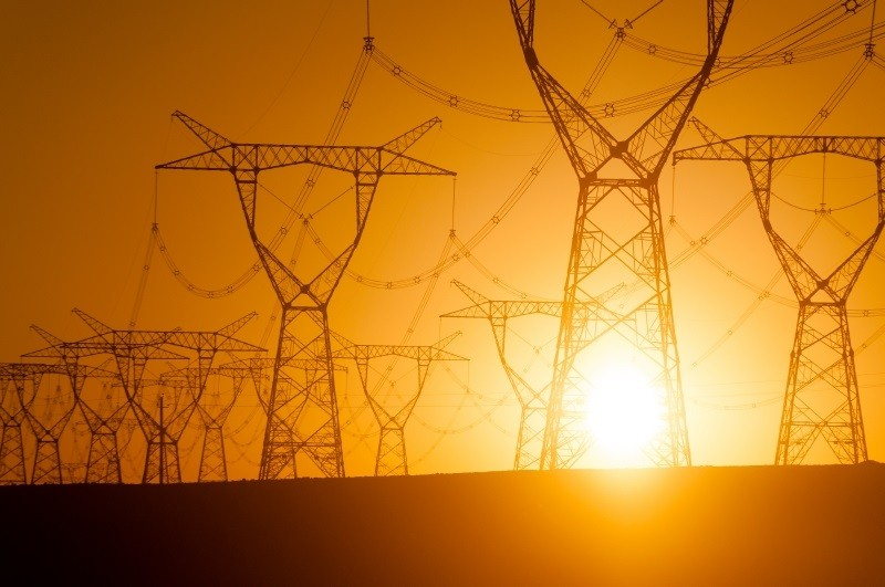 Sun behind electrical towers