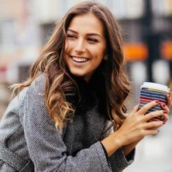 Lady smiling and holding a coffee in the city