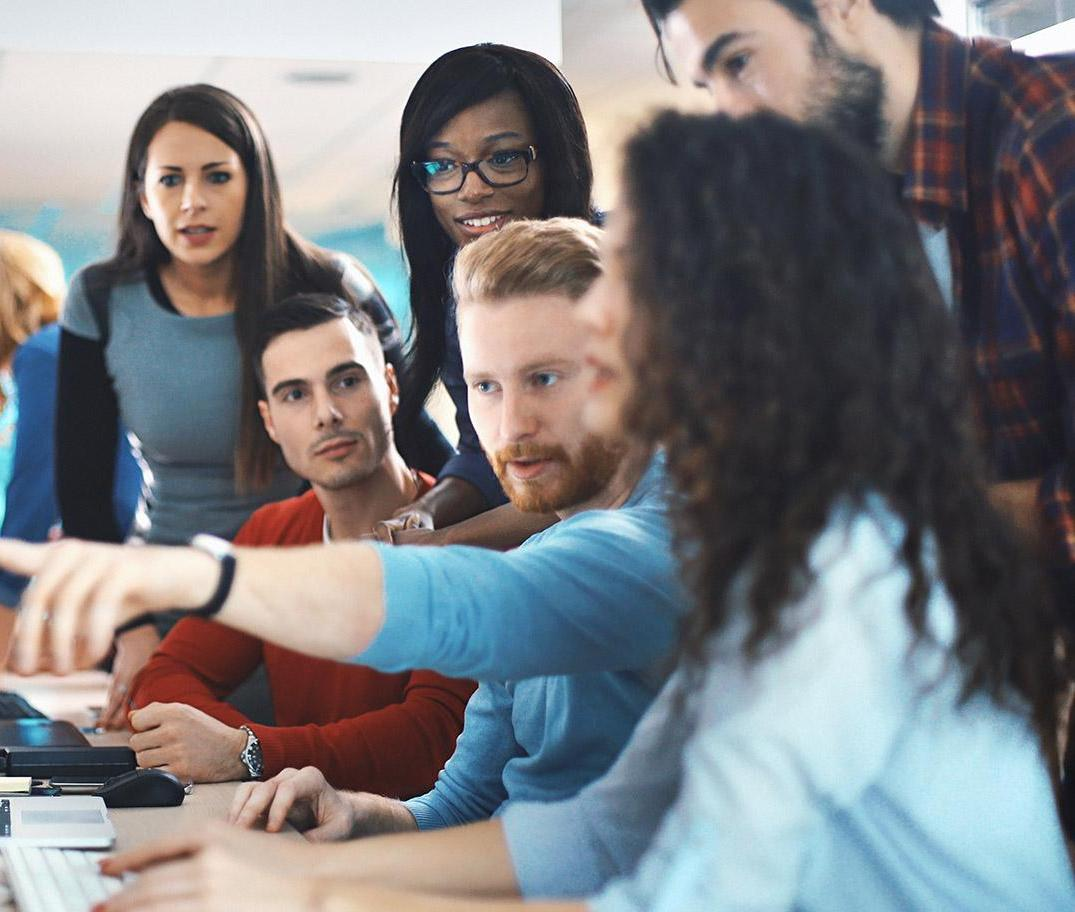 Group of young coworkers having discussion around computer