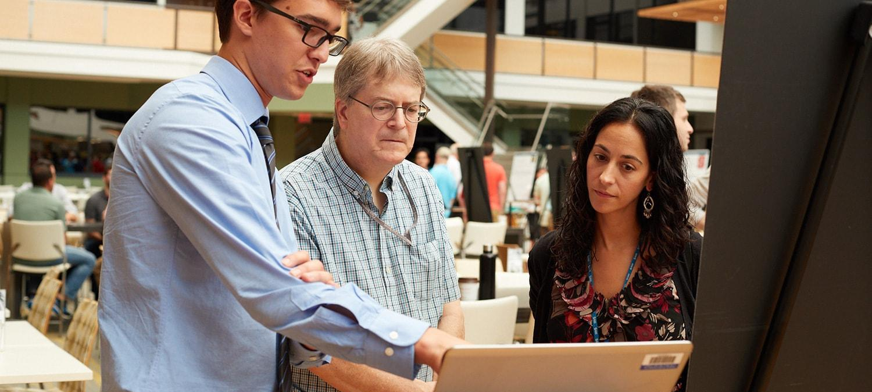 SAS intern presenting work to two employees