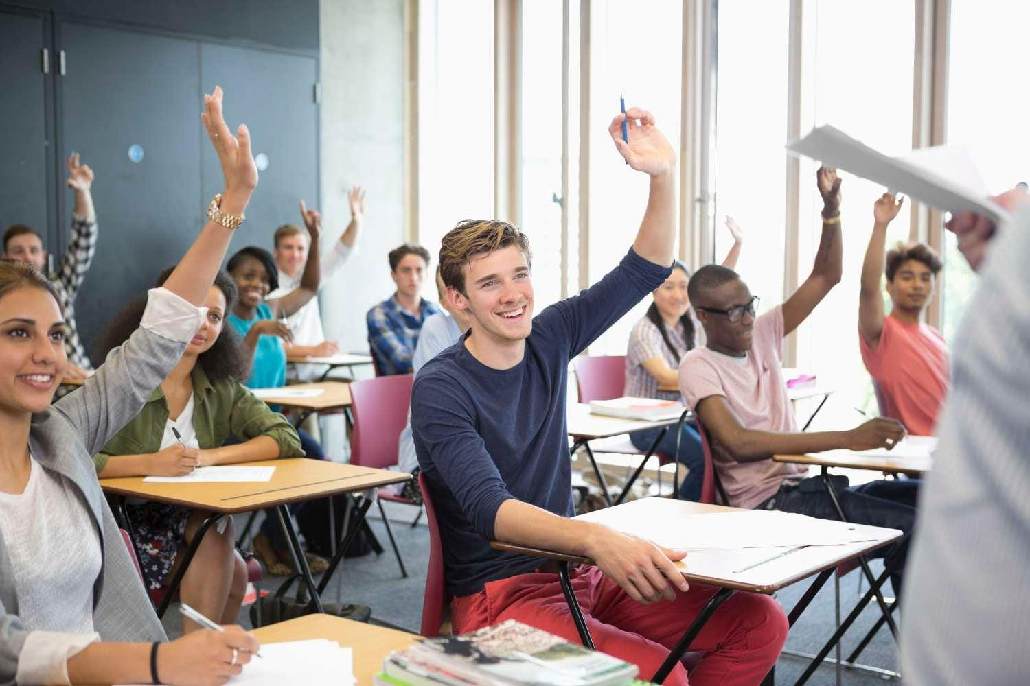 Group of high school students raising hands in a classroom