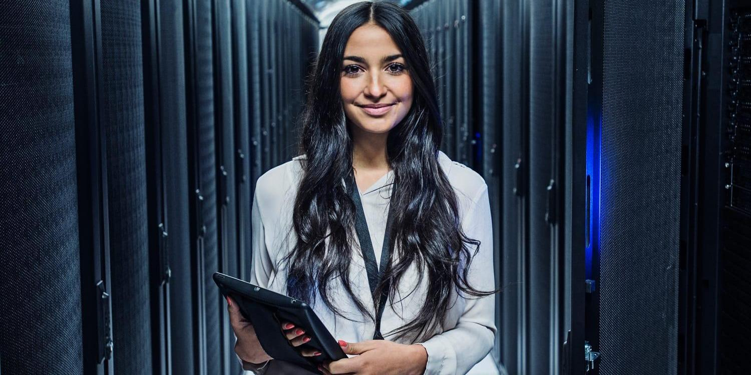 Young female data analyst with tablet in server room