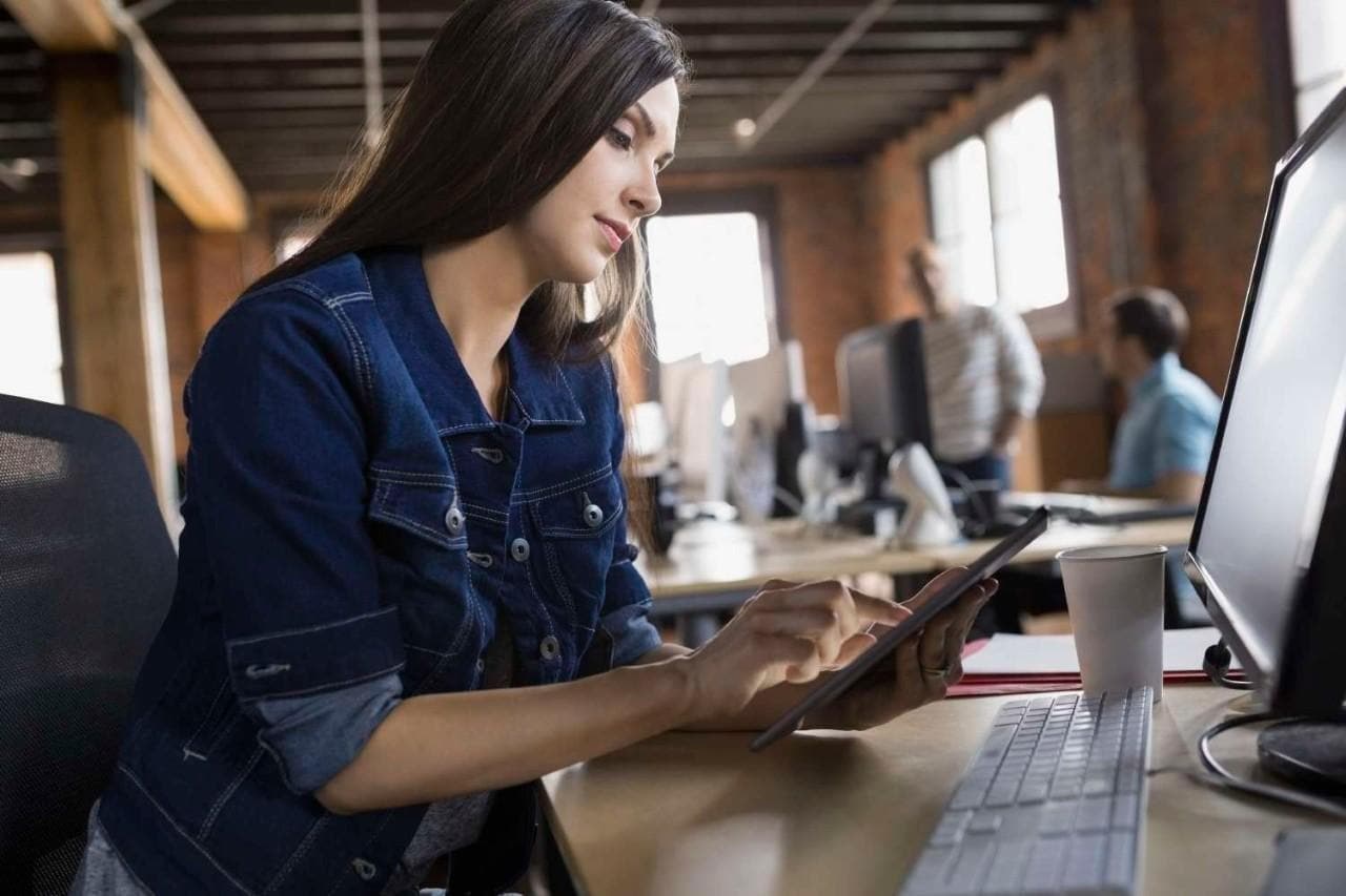 Businesswoman using digital tablet at desk in office