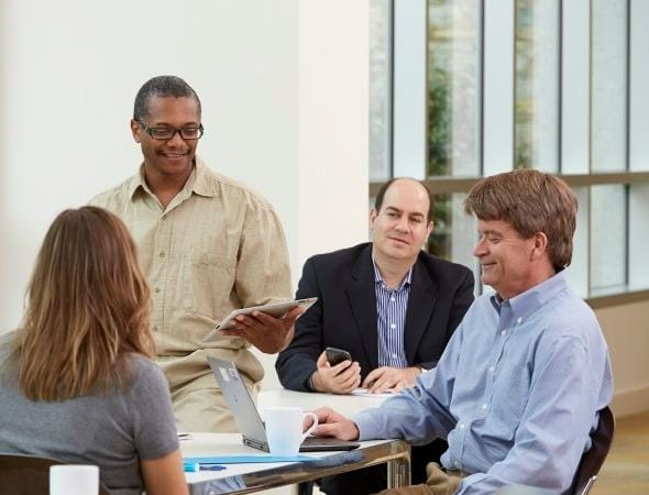businessman-leads-meeting-with-tablet