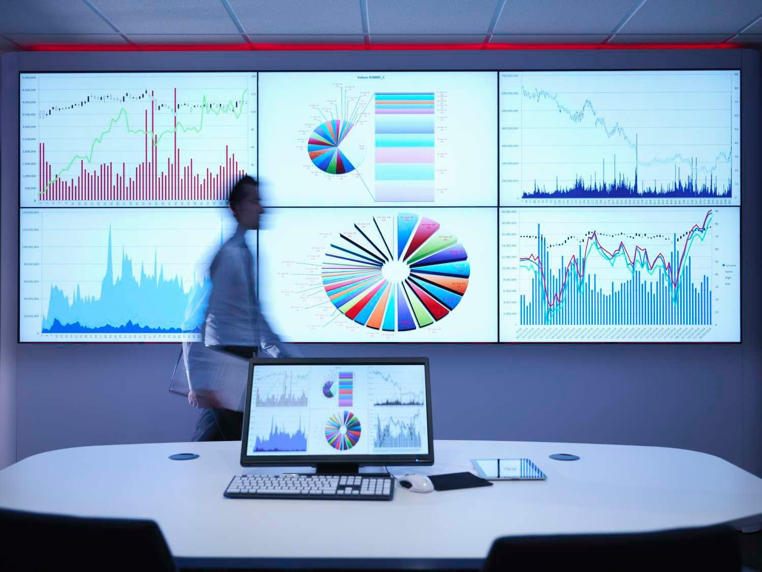Businessman walking in front of graphs on screen