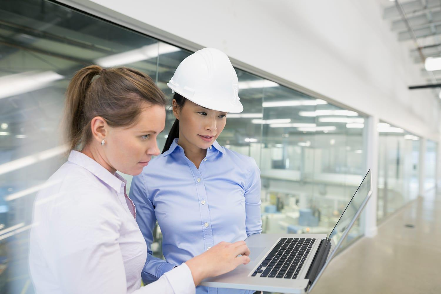 Engineers with laptop in factory