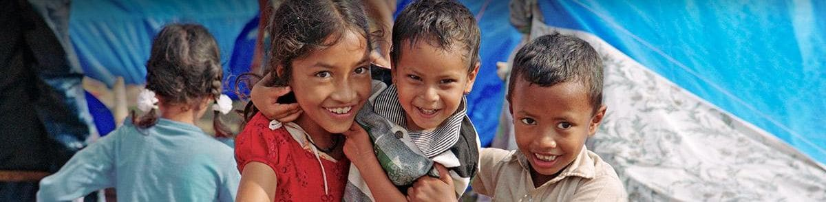 Three children smiling during relief efforts in Nepal