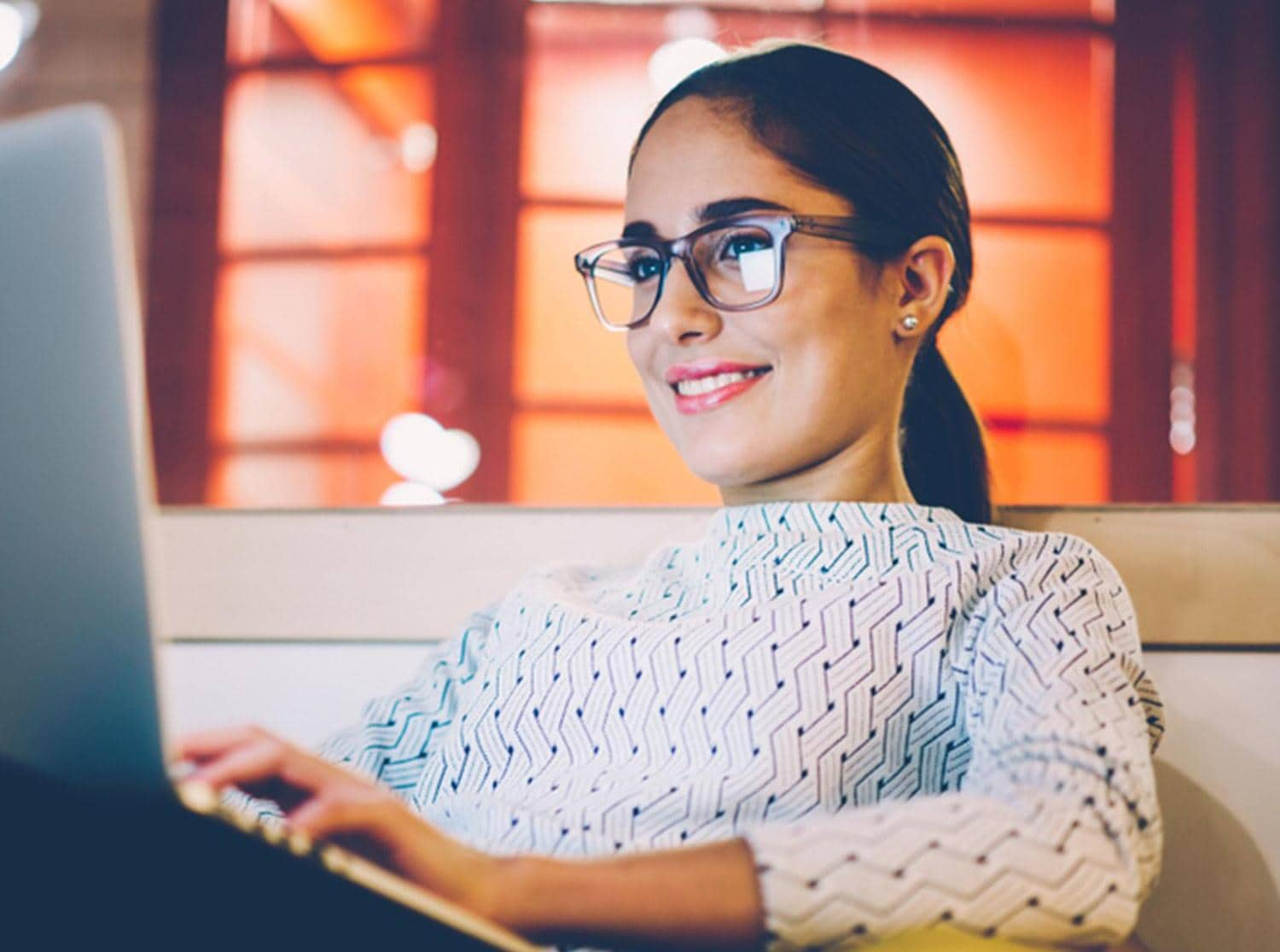 Woman with glasses on laptop smiling