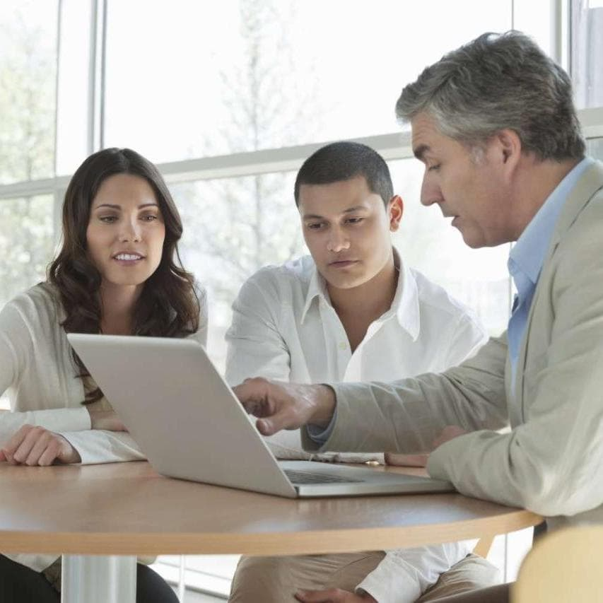 Three midmarket bank colleagues looking at laptop