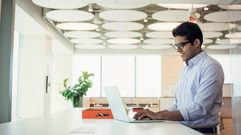 Businessman working at high desk using laptop