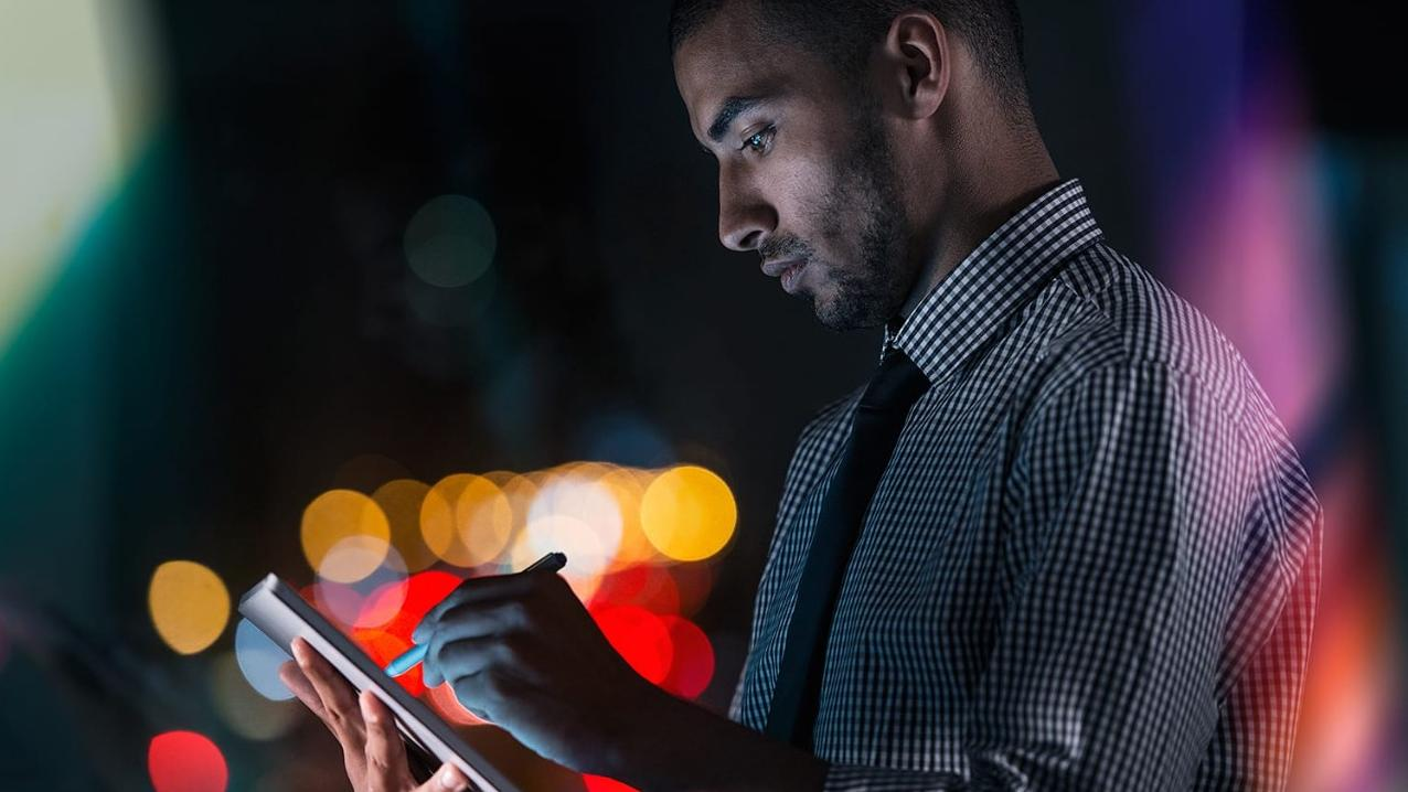 Young businessman using his tablet while working at night