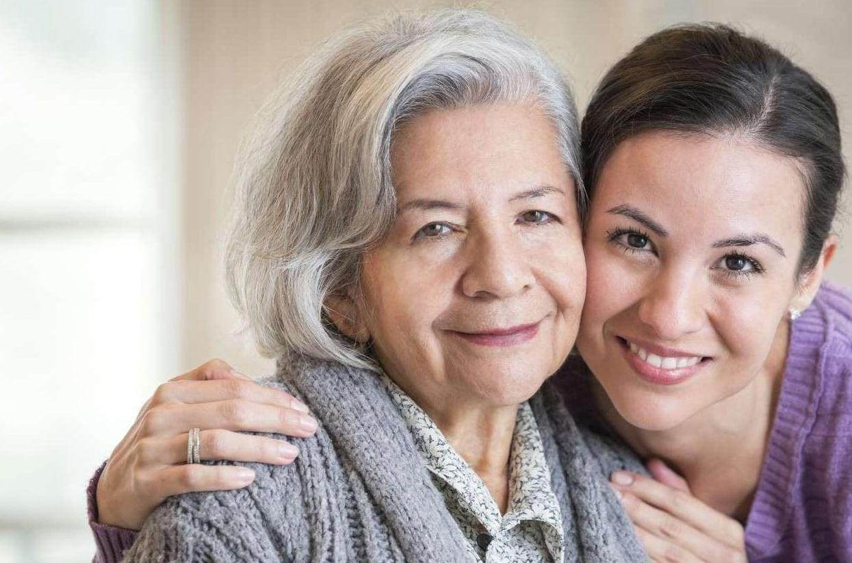 Woman wrapping her arms around her elderly mother and smiling at camera