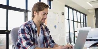 man-looking-at-laptop-with-plaid-shirt