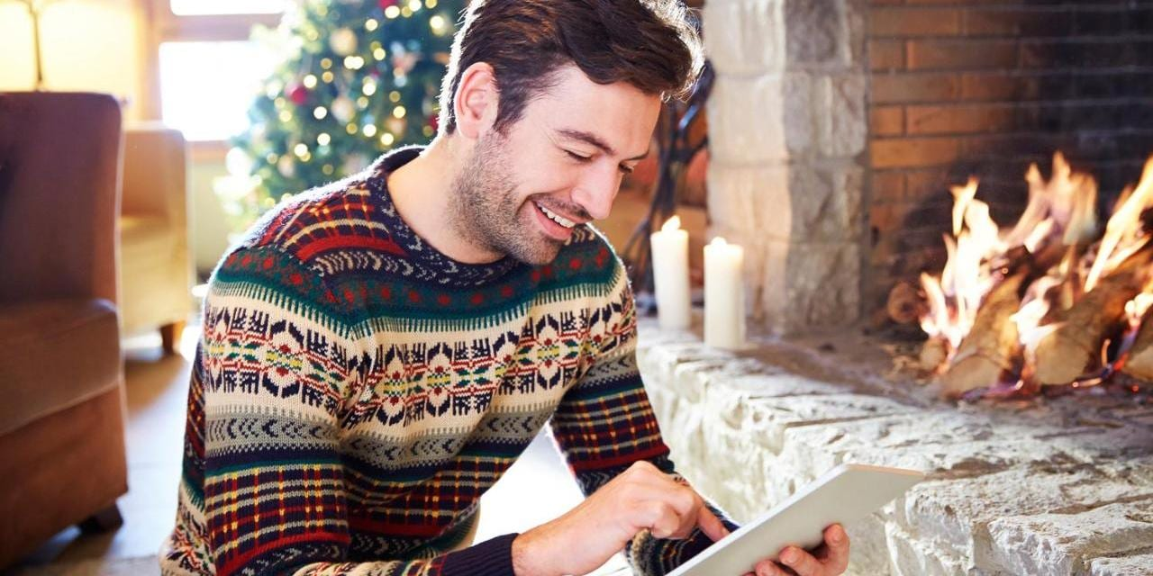 Man in winter sitting in front of a fireplace with iPad, christmas tree in the back