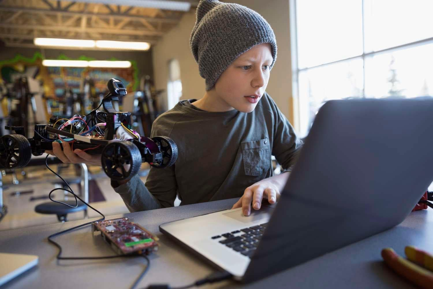 Young male student uses laptop to program remote control car
