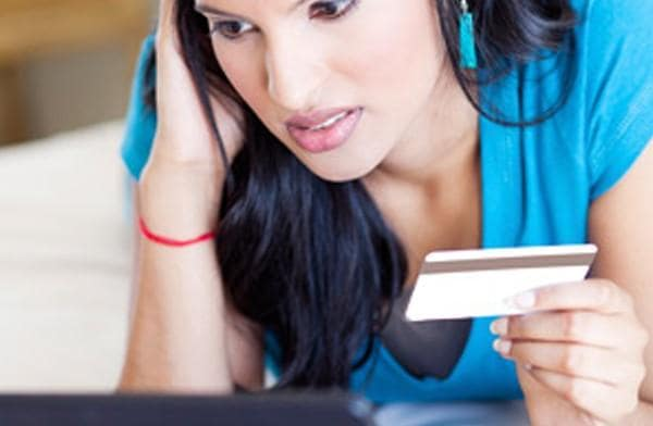 worried woman holding credit card
