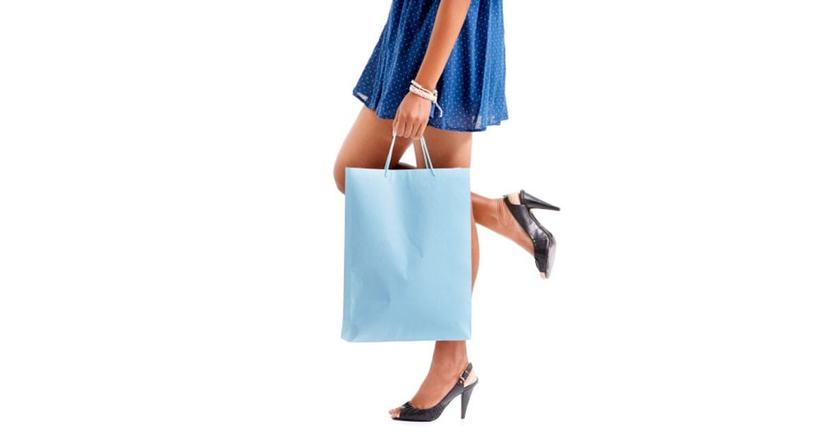 Consumerism lifestyle -- a close up of a woman legs in heels holding a shopping bag