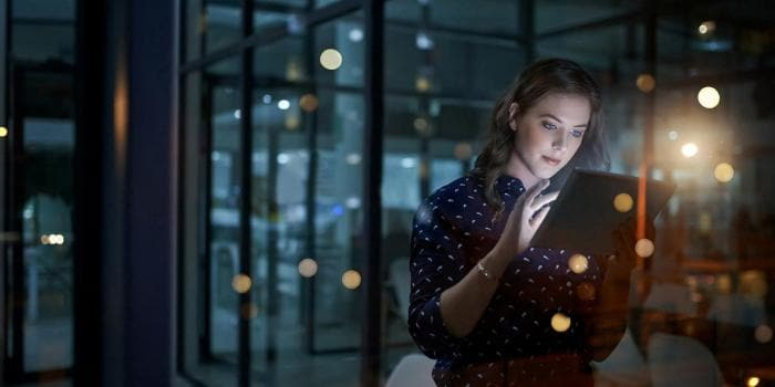 Businesswoman using laptop at night outside office building