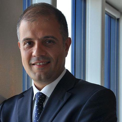 Akbank T.A.Ş Analytics Senior Vice President Dr. Attila Bayrak standing interior by windows
