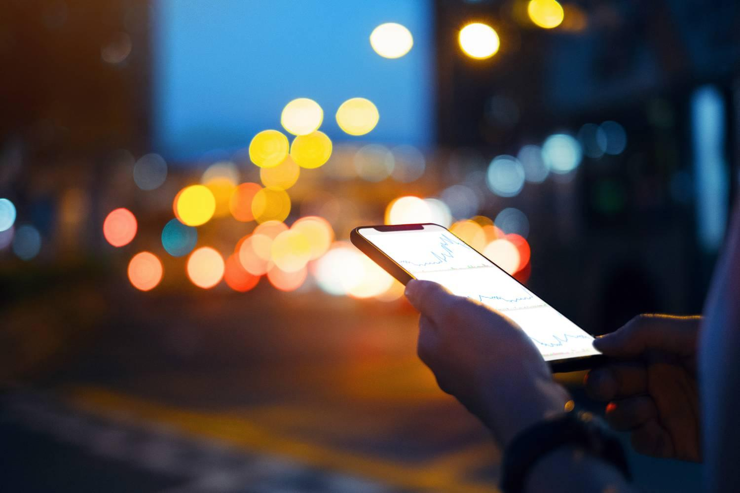 Close up of hands checking financial trading data on smartphone in city street at night