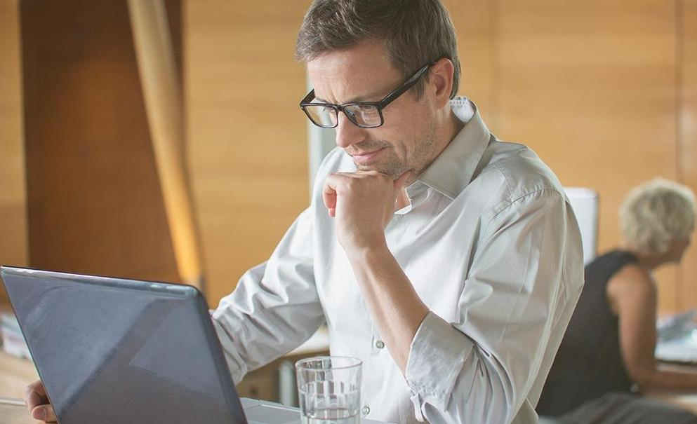 Satisfied business man working at laptop