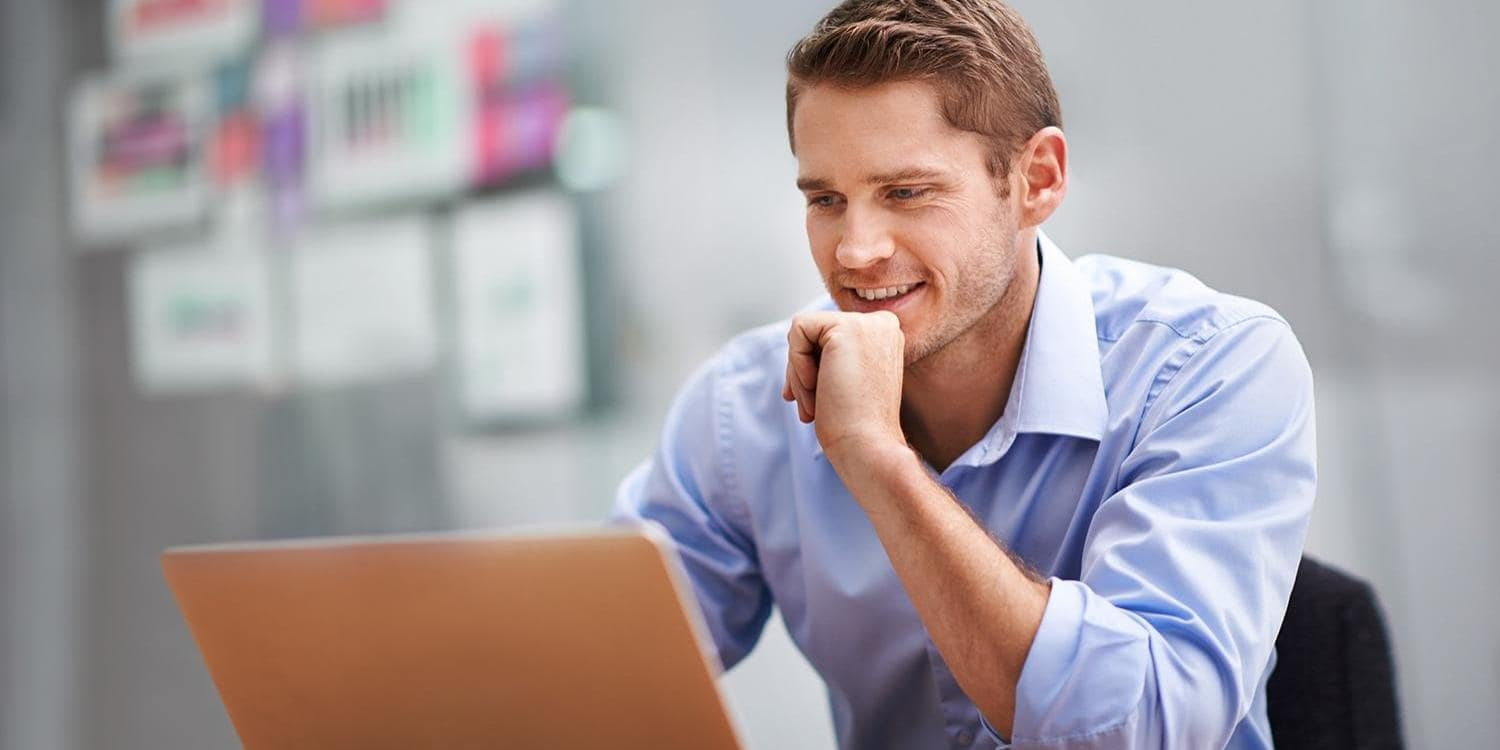 Confident young business man at laptop