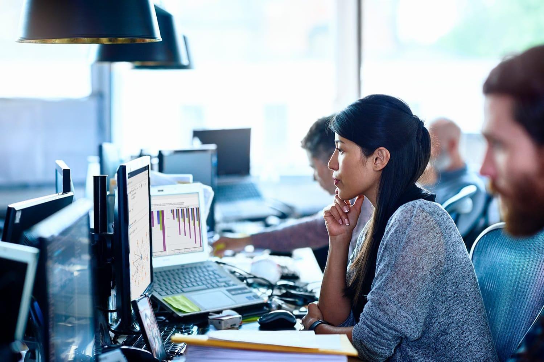 Team of data scientists working at desks in modern office