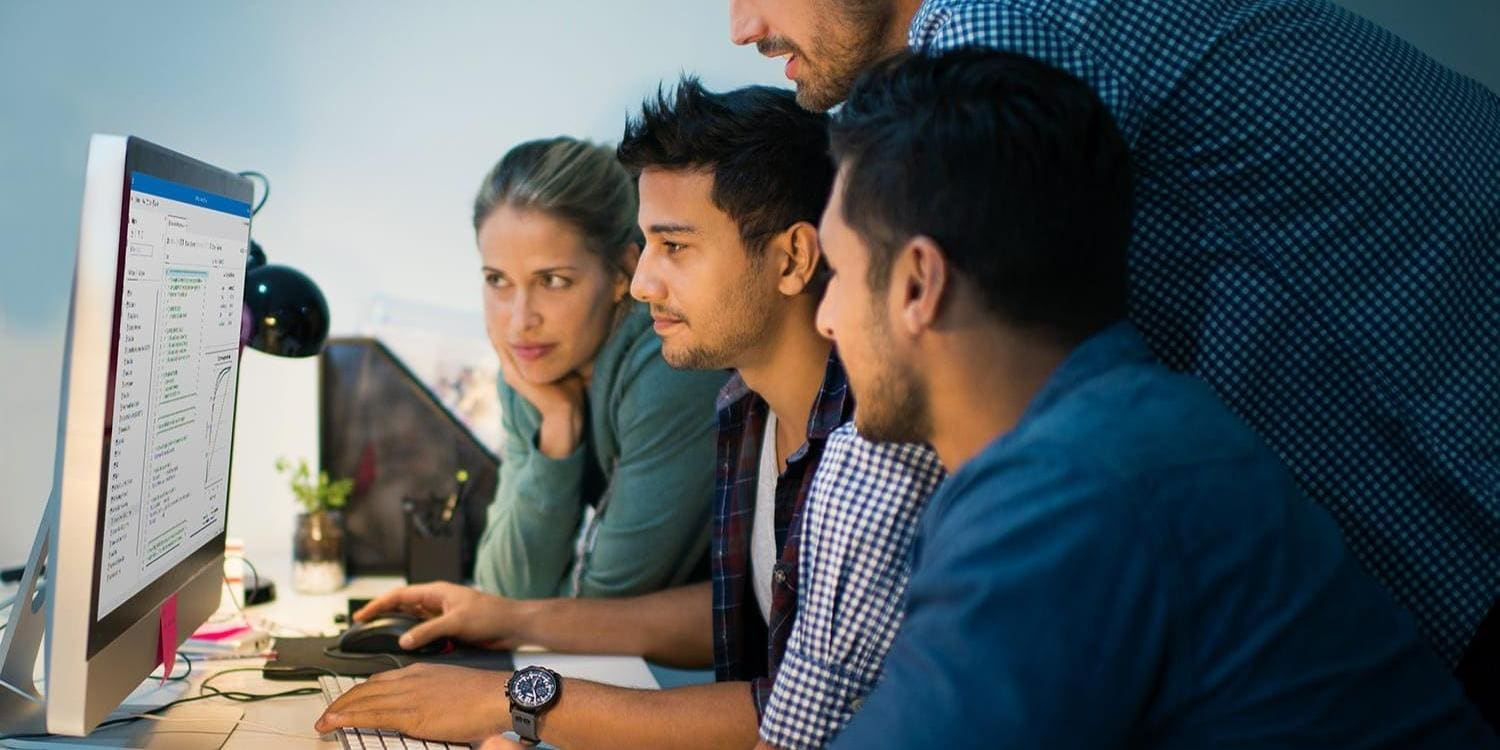 Four colleagues gathered around a computer