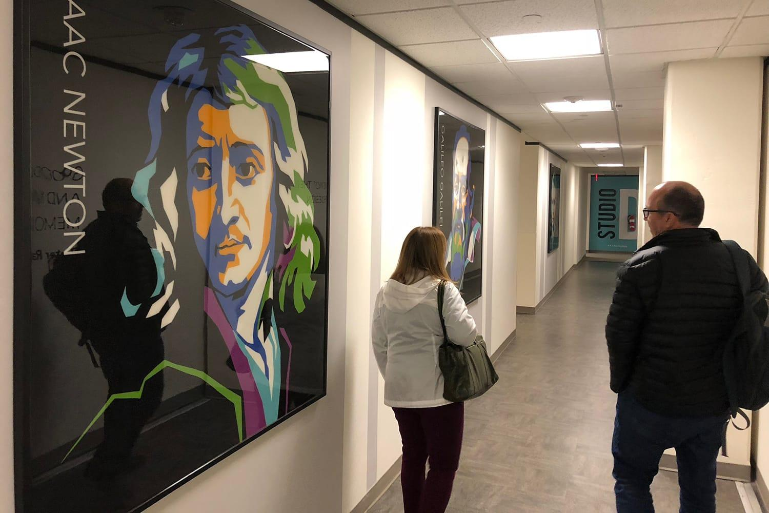 Two employees walking down the design center hallway