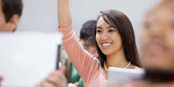 Female college student raising hand and smiling in classroom