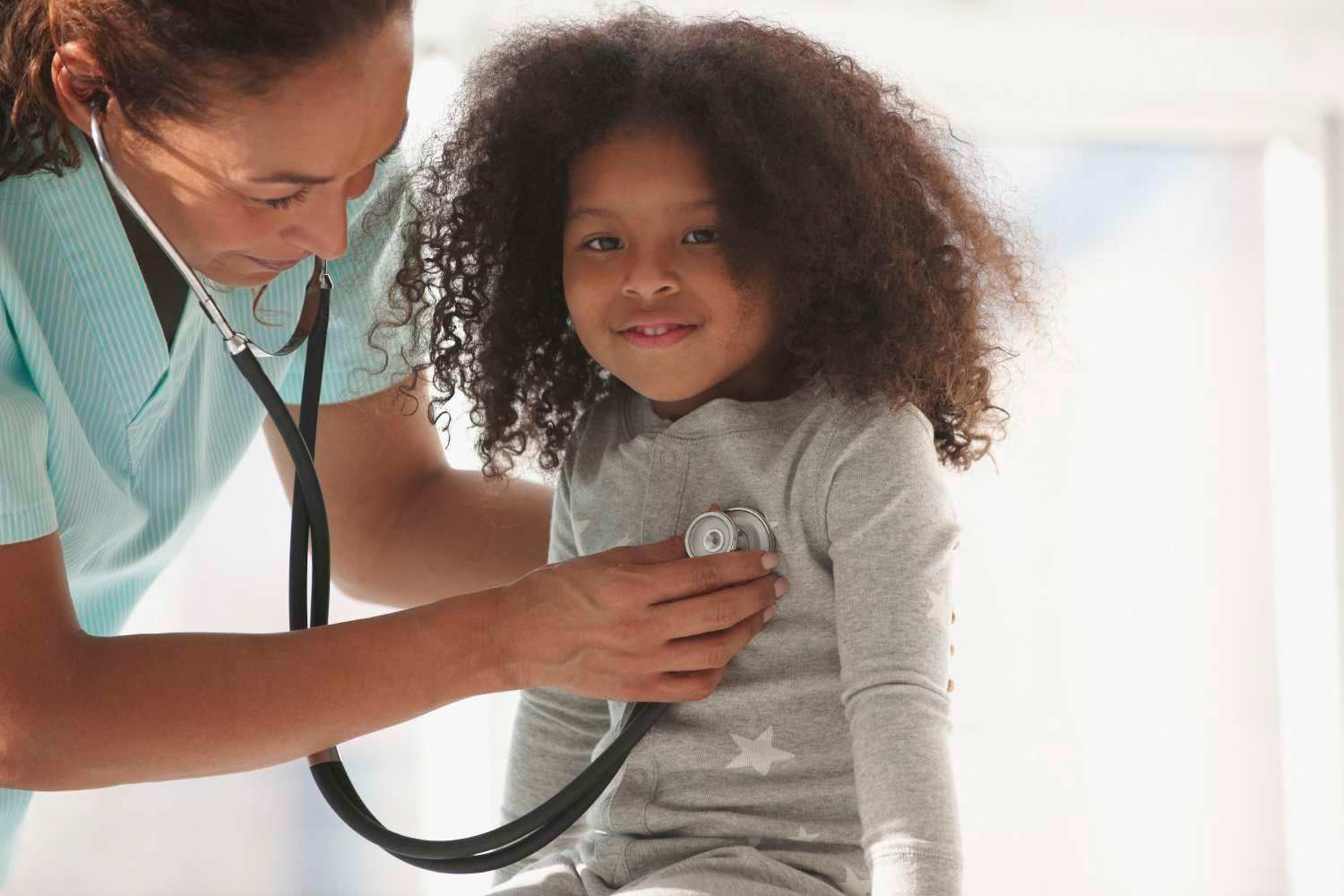Female Doctor examining a child with stethoscope