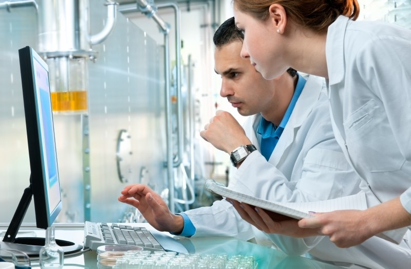 Scientists look at computer in a lab