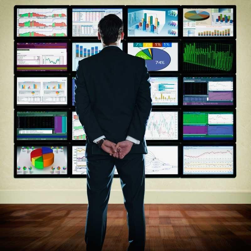 man looking at wall of charts