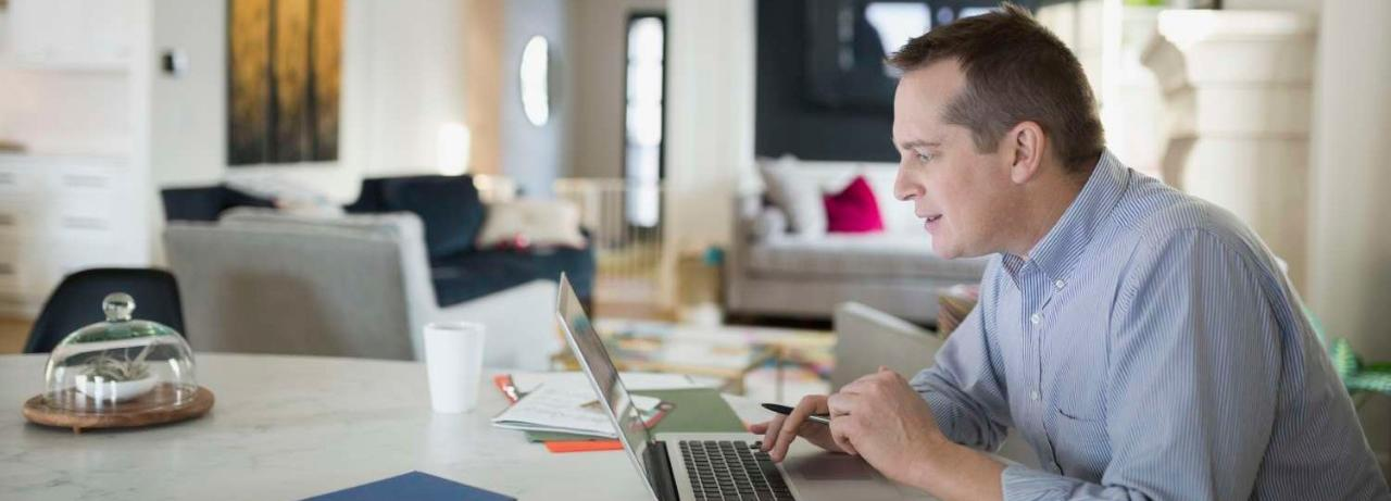 Man working on laptop on kitchen table