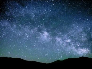 Starry night sky behind silhouette of mountains